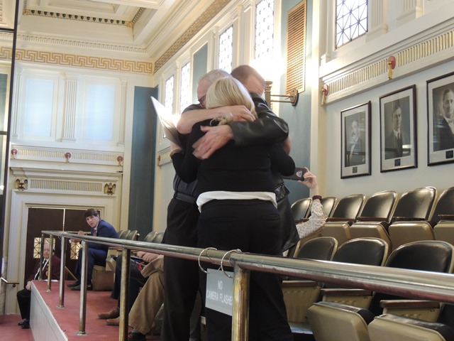 Francine Frost's husband, Malcolm Frost, daughter, Vicki Frost Curl and grandson, Cory Curl, hug after the Francine's Law was approved by the full Senate.